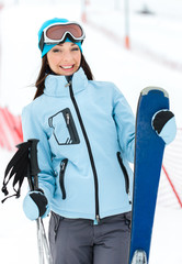 Half-length portrait of female who has skis in hands