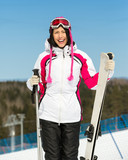 Half-length portrait of female skier standing with skis