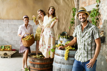 farmer drinks wine while women pounding grapes in an old farm