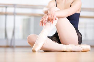Close up shot of legs of sitting on the floor ballerina
