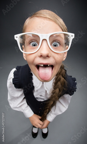 Wide angle portrait of little girl in glasses tongue gesturing