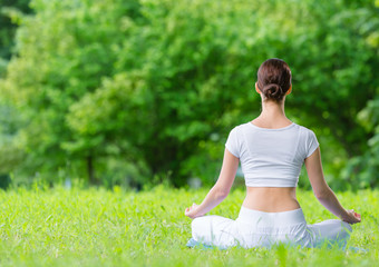Backview of woman who sits in lotus position zen gesturing