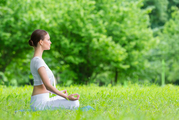 Profile of woman with closed eyes who sits in asana position