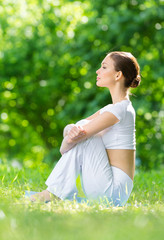 Profile of woman sitting on mat in park after exercising