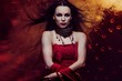 Beautiful vampire woman in red dress with waving hair