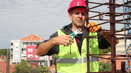 Construction Worker in Action With Combination Pliers.