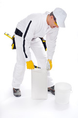worker in white overalls holding a knive tools packag