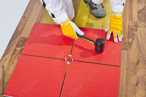 Worker Applies with Rubber Hummer Tile on a wooden Floor reinfor