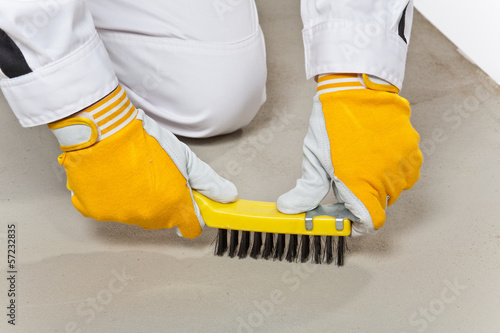 Worker with wire brush cleans the cement base