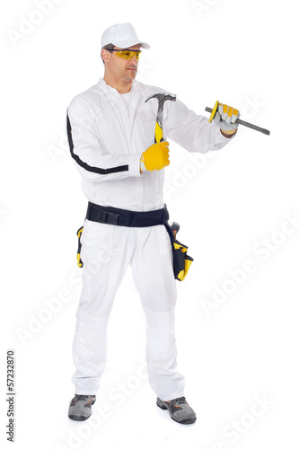 worker in white overalls working with hammer and chisel
