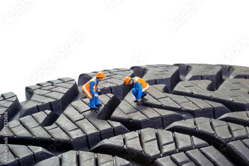 Miniature workers checking the depth tread on a car tyre