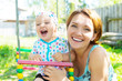 Happy mother with laughing baby sits on swing