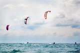 Three kitesurfers enjoying the surf.