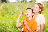 mother and son in the park blowing soap bubbles