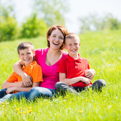 Young happy mother with children in park