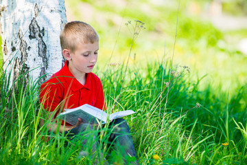 Schoolboy reading the book at  nature