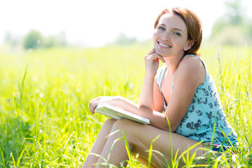 Pretty smiling woman reads the book at nature