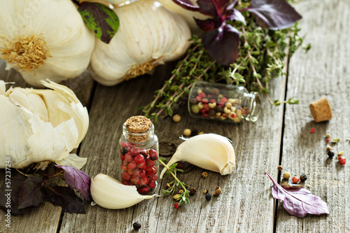 Garlic, herbs and spices on a wooden table