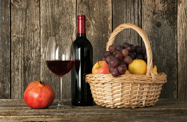 Still-life. Bottle of red wine, glass and basket with fruit