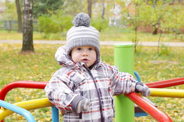 baby outdoors in autumn on playground