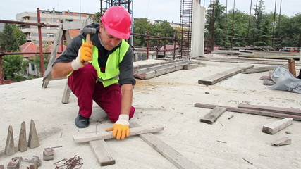 Manual Worker Using Hammer at Construction Site.