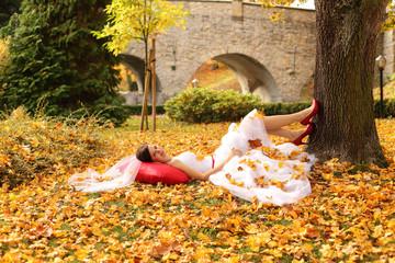 Piękna panna młoda w jesiennych kolorowych liściach.