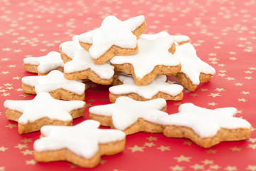 Many star shaped cinnamon biscuits on red background