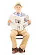 Senior gentleman on a wooden chair holding a newspaper