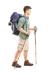 Full length portrait of a hiker with backpack and hiking poles w