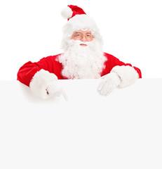 Santa claus posing behind a blank billboard and pointing