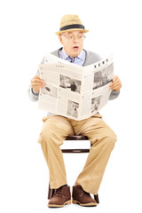 Senior gentleman in shock on a wooden chair reading a newspaper