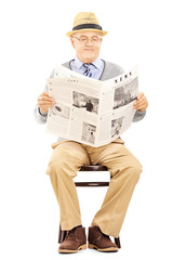 Senior gentleman reading newspaper and sitting on a chair
