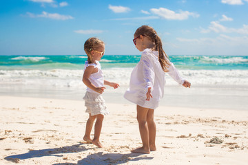 Two little sisters in white clothes have fun at tropical Mexico