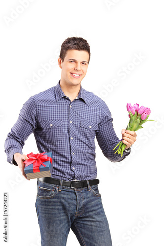 Handsome young man holding tulips and gift box