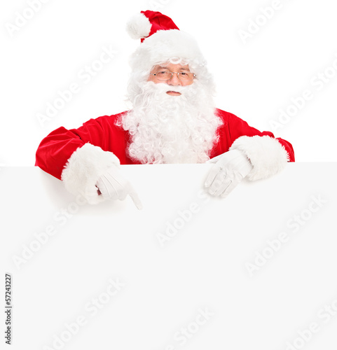 Santa claus posing behind a blank billboard and pointing