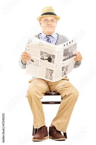 Senior gentleman on a wooden chair holding a newspaper
