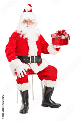 Smiling Santa Claus on a chair holding a present