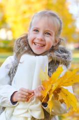 Little smiling girl with fallen autumn leaves