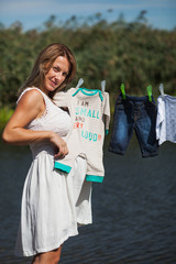 Pregnant woman holding baby clothes