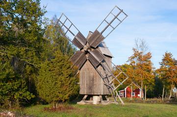 Alte Windmühle vor roten Holzhaus auf Öland, Schweden