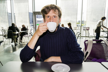 Young man drinking coffee in a cafe