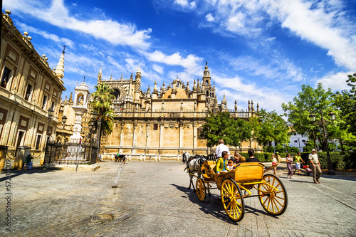 Carriage near Cathedral with Giralda tower, Seville, Spain.