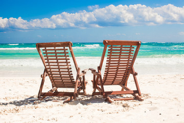 Beach wooden chairs for vacations and relax on tropical white