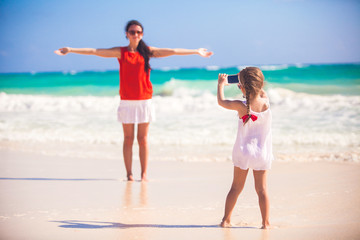 Little girl photographs her mother on the beach