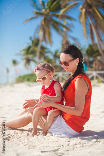 Little girl relaxing on the beach with her young mom