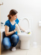 housewife in blue cleaning toilet bowl