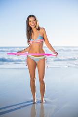 Happy woman in bikini playing with hula hoop