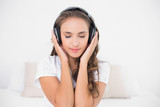 Content attractive brunette listening to music with closed eyes