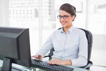 Pleased classy brown haired businesswoman using a computer