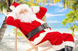 Relaxed Santa Claus seated on a chair, on a beach with palm tree